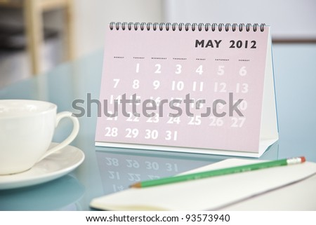 Desktop calendar sitting on a glass desk showing the month of May 2012