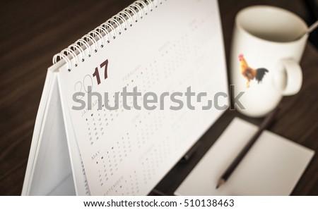 Desktop calendar sitting on desk showing year of 2017.
