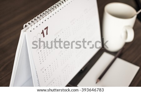 Desktop calendar sitting on desk showing year of 2017. Table, Coffee, Paper, Pencil, January, Start, Work, School, Student, History, Teacher, ROI, Date, Plan, Cup, Drink, Holiday, Thinking concept. #393646783