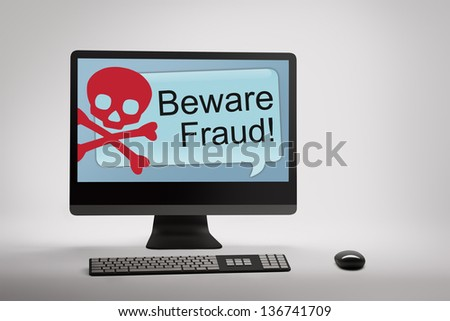 Desktop computer displaying conceptual internet fraud and scam warning on screen