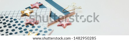 Desktop feminine composition with patterned notepads, golden stars and deer clips on white table with sun light and shadows. Toned Close up concept for blogger
