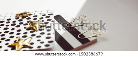 Desktop feminine composition with patterned notepads, golden stars and deer clips on white table with sun light and shadows. Close up concept for blogger