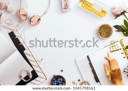 Desktop flatlay scene, with white open planner, desk tidy tray, gold and rose gold stationery accessories, jewellery, pink peony, featuring a female hand holding a gold pen