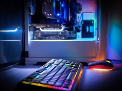 Desktop gaming PC and backlit keyboard. Components of the computer. PC case with RGB light, blurred background