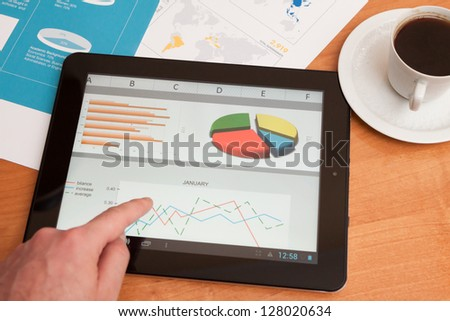 Desktop in stock exchange office with a tablet pc showing stock market chart.