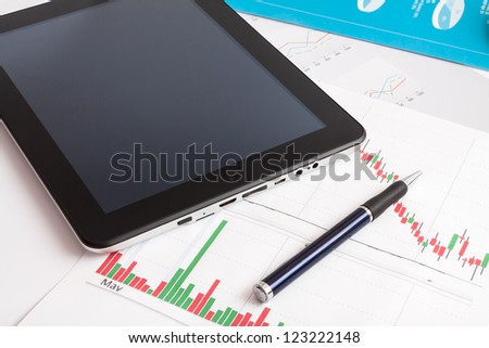 Desktop in stock exchange office with a tablet  showing stock market chart.