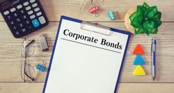 Desktop office desk, notebook, glasses, pen and documents with Corporate Bonds on a tabl