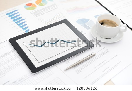 Desktop with bad statistic report on a modern digital tablet, some papers with charts and graphs and with cup of coffee.
