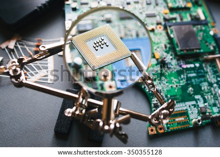Desktop with broken disassembled laptop. Electronic parts of pc: motherboard, microprocessor. Analysis computer cpu through magnifying glass.