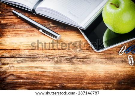Desktop with paper agenda, digital tablet and green apple