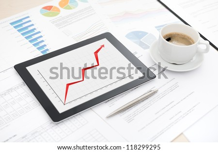 Desktop with success business report on a modern digital tablet, some papers with charts and graphs and with a cup of coffee.