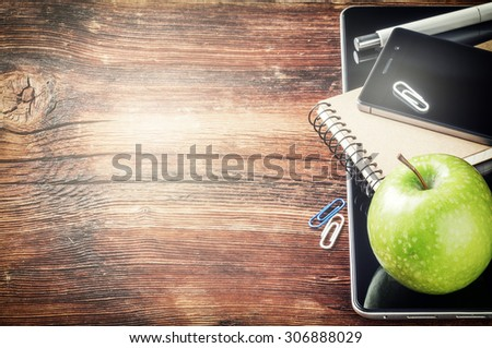 Desktop with tablet pc, smartphone and green apple. Copy space