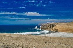 desolate and vast landscape of Paracas at the coastline of Peru, a place were desert meets the ocean. Showing blue sky, clouds and a sandy desert beach
