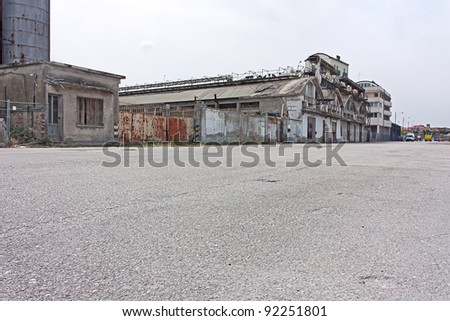 desolated street on the docks of port - desert suburbs of the city with abandoned warehouses and factories