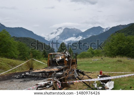 Desolation in front of greatness. A burnt car facing a great mountain