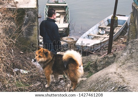 Despair and loneliness - a man and his dog watching old boats on Danube river #1427461208