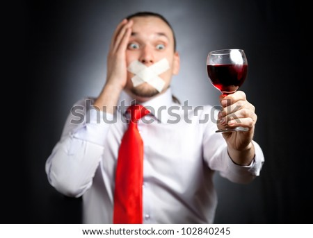 Despair Businessman with plaster on his mouth in red tie holding the glass of red wine and at black background. Represents outcry alcoholic dependency