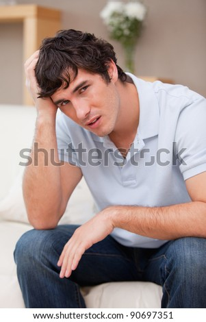Despaired young man sitting on the couch