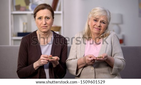 Desperate aged women looking camera holding coins, financial instability crisis