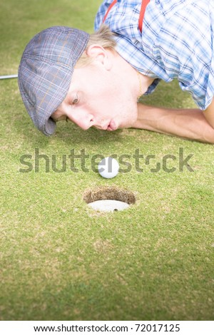 Desperate And Frantic Golfer Attempting To Inch His Green Ball Closer To The Golfing Hole By Blowing On It In A Humorous And Funny Golf Cheating Concept - stock photo