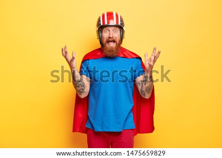 Desperate bearded man gestures in stressful situation, has no way out, looks with embarrassement, wears headgear, superhero suit, has tattoo on arm, poses against yellow background. Bad emotions