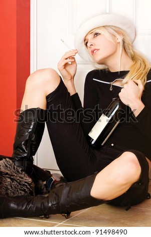 Desperate blond woman with cigarette and bottle of wine, seating near someone's door on a New Year's evening