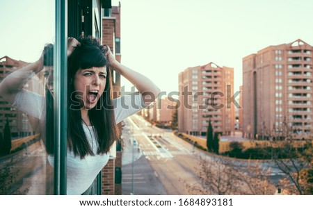 Desperate bored woman peeks out the window during quarantine over covid-19 crisis. Stay at home concept. Empty city under confinement. Domestic abuse and violence. Valladolid, Spain.