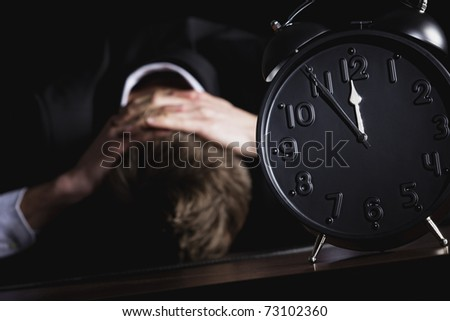 Desperate business person in dark suit sitting at office desk with head down being in despair with close up of alarm clock in foreground showing five minutes to twelve, isolated on black background.