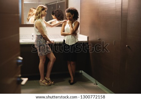 Desperate business woman in office bathroom, crying for bad news and hostile work environment. A young friendly colleague is supporting and listening to her.