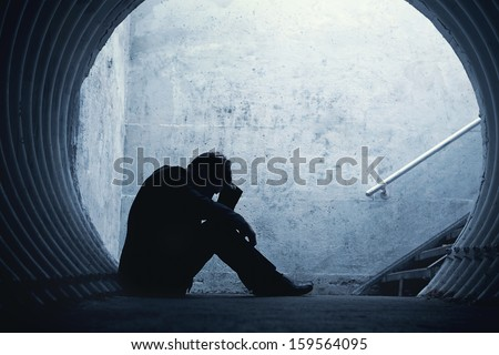 Desperate Businessman in silhouette lying on the ground and holding his head in a dark tunnel. With room for your text