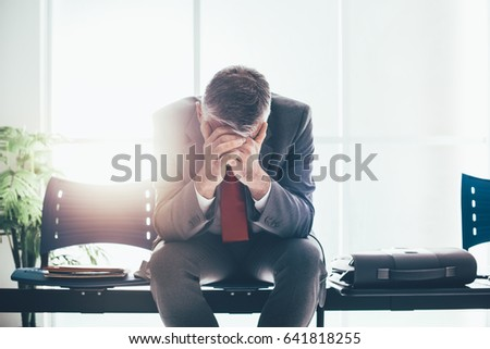 Desperate businessman in the waiting room with head in hands, he is waiting for a job interview; unemployment and business failure concept