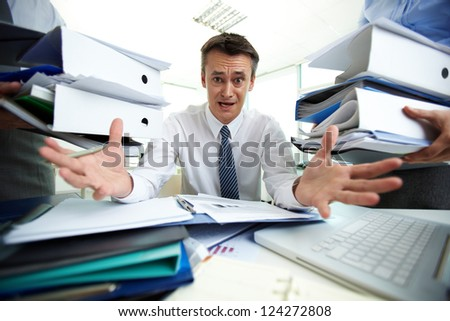 Desperate businessman not knowing what to do with all paperwork