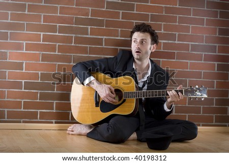 desperate businessman sits with a guitar on the floor and sings fort money