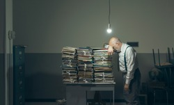 Desperate businessman with lots of paperwork in his messy office at night, he is leaning on a pile of files, bureaucracy and deadlines concept