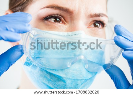 Desperate devastated female doctor,eyes full of tears,crying & grieving over loss of patient,Coronavirus COVID-19 virus disease causing many death cases,tragic consequences,victims of global pandemic