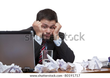 Desperate, frustrated man sitting with paperwork at desk in office. Isolated on white background.