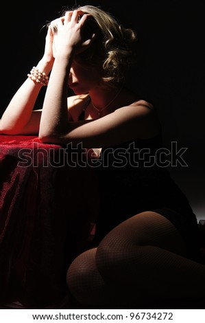desperate girl sitting on a dark background