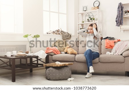 Photo of  Desperate helpless woman sitting on sofa in messy living room. Young girl surrounded by many stack of clothes. Disorder and mess at home, copy space
