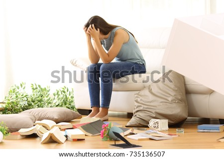 Desperate homeowner complaining after home robbery sitting on a couch of the messy living room at home
