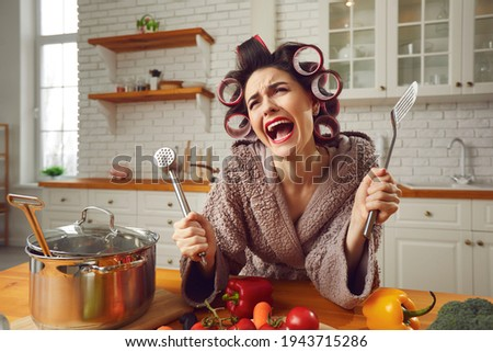 Desperate housewife sick and tired of cooking and housework crying in the kitchen. Unhappy overworked young woman in hair rollers and bathrobe complaining about everyday cooking food and cleaning home Photo stock ©