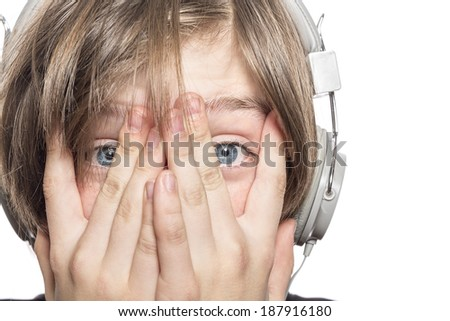 desperate male teenager with headphones covering his face with hands, isolated on white