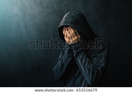Desperate man in hooded jacket is crying, hands are covering face and tears in the eyes, light of hope shining from his right side