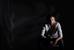 Desperate man sitting alone in dark room