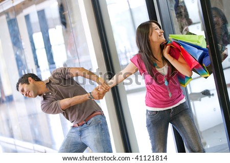 desperate man trying to take his girlfriend out of a retail store