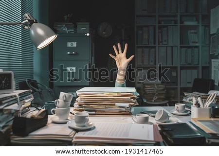 Desperate office worker overwhelmed with paperwork, she is asking help with her hand Stock photo ©