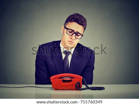 Desperate sad business man waiting for someone to call him  #755760349