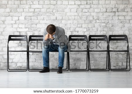 Desperate sad jobless man put head on hands sitting on chair hunched after unsuccessful failed job interview meeting. Fired employee feels stressed after dismissal, boss and company bankruptcy concept