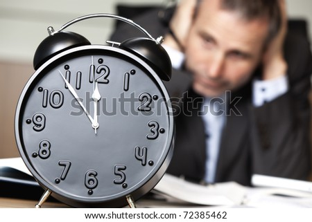 Desperate senior businessman being close to ruin - clock showing five minutes to twelve.