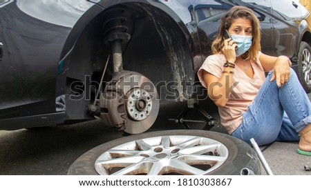 Desperate woman because of her punctured car wheel Foto stock ©