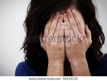 Desperate woman covering her face with her hands